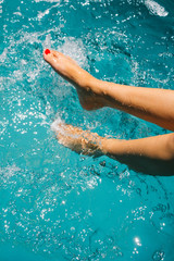 Legs in the water of a woman sitting on the edge of a swimming p