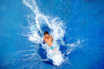 man jumping in pool, huge splash, top view Wall mural