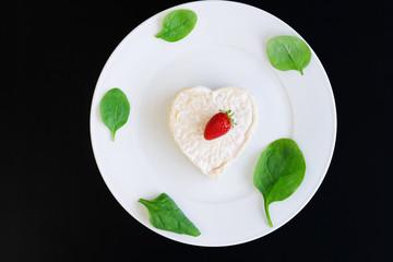 сыр в форме сердца на белой тарелке с салатом и клубникой