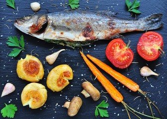 baked fish with vegetables on a black background