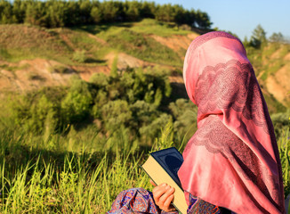 Muslim Woman Reading Holy Quran, outdoors