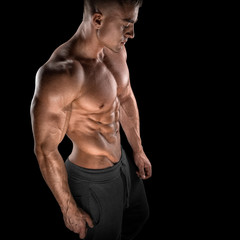 Muscular and fit young bodybuilder fitness male model posing