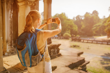 Female tourist with smartphone taking picture of Angkor Wat