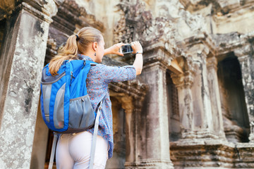 Female tourist with smartphone taking picture in Angkor Wat