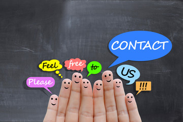 Contact us concept with happy fingers on blackboard background