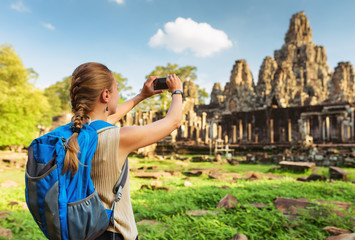 Fototapete - Young female tourist taking picture of Bayon temple, Angkor