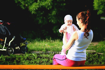 a child with her mother sitting on a bench