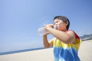 青空とビーチと水を飲む子供