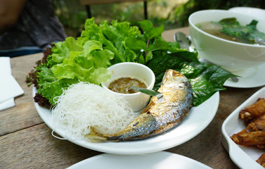 Thai style fried mackerel fish serving with fresh salad and spic