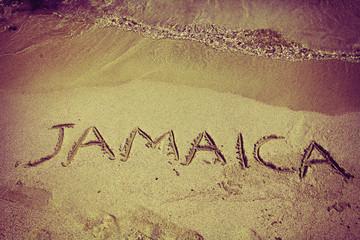 retro inscription Jamaica on beach sand