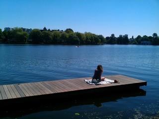 Frau sitzt auf Steg und liest allein Sonne