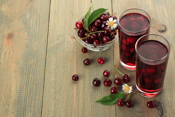 Closeup of fresh juice with sweet cherries on a wooden background
