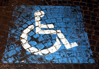 symbol of handicapped parking painted on porphyry in the street