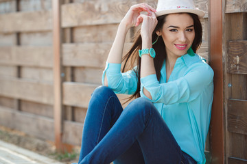 Attractive young woman sitting near the wooden fence