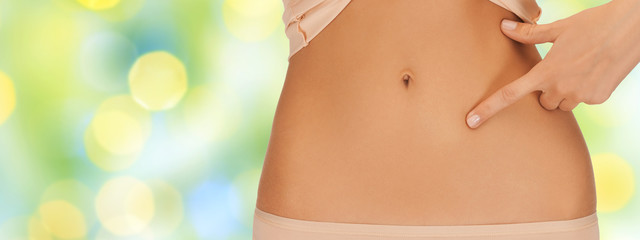 close up of woman pointing finger to bare belly
