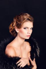 Elegant young woman in black lingerie posing at studio.