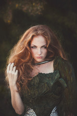 Beautiful woman with red hair in fashion military clothing