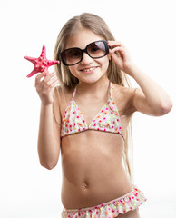 happy smiling girl in sunglasses posing with red starfish