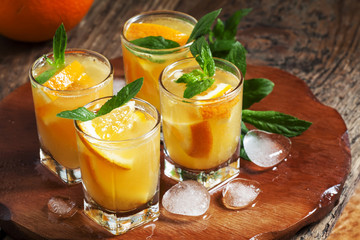 Refreshing cocktail with soda, orange, mint and ice, selective f