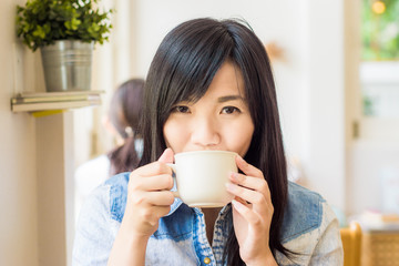 Woman with cup of coffee smiling in cafe
