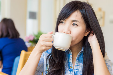 Young lovely asian woman drinking coffee