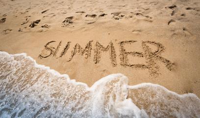 """""""Summer"""" written on wet sand at seashore"""