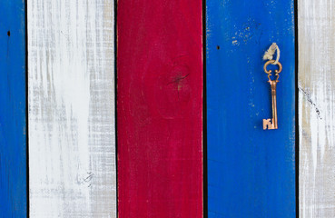 Skeleton key hanging on red, white and blue wood background