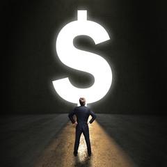 Geschäftsmann steht vor einem leuchtenden Dollar-Durchgang