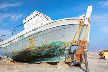 Old veteran ruined fishing boat in beach shore on Greek Kos island Mastihari bay