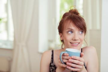 entspannte junge frau trinkt eine tasse tee zuhause