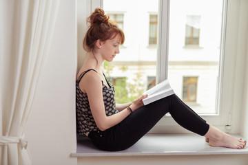 frau sitzt auf der fensterbank und liest ein buch