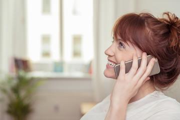 moderne junge frau telefoniert zuhause mit ihrem handy