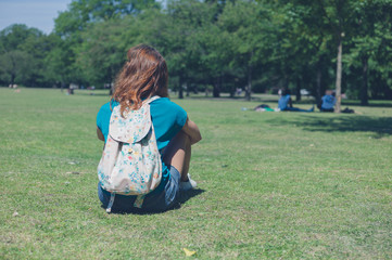 Young woman with backpack relaxing in park