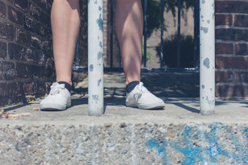 Legs of young woman by bars