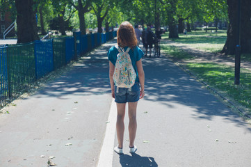 Young woman with backpack in park