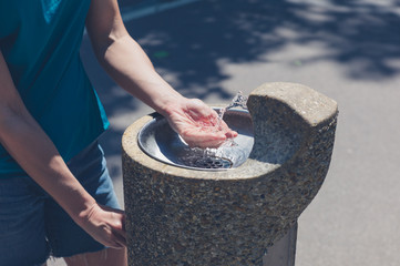 Young woman by water fountain