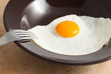 view of a fried egg served on dark dish with fork