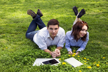 Young people working out. Man and woman casual dress code pant jeans shirt lying on grass lawn working with laptop computer tablet PC book students learning businessman out of office