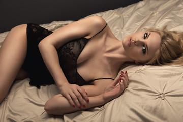 Sensual blonde woman posing in dark sexy lingerie.