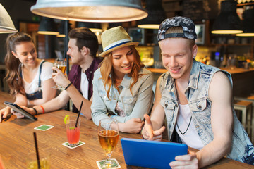 happy friends with tablet pc and drinks at bar