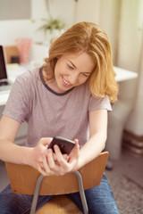 studentin sitzt zuhause am schreibtisch und schaut auf ihr handy