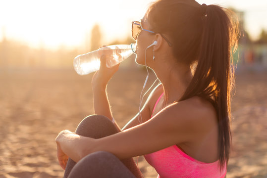 Beautiful fitness athlete woman drinking water after work out