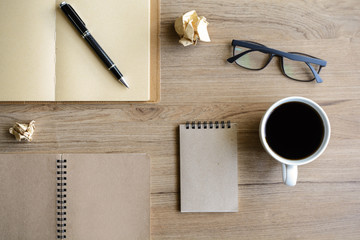 Cup of coffee with notebook on desk