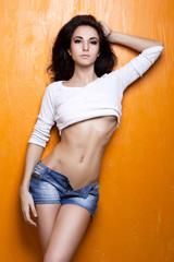 Sexy female model posing on orange background