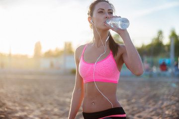 Beautiful fitness athlete woman resting drinking water after