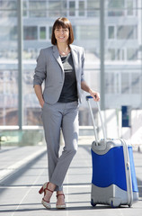 Smiling business woman standing at airport with bag