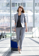 Happy business woman walking with suitcase at airport
