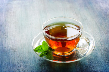 Wall Mural - Cup of tea with mint leaf on dark rustic background