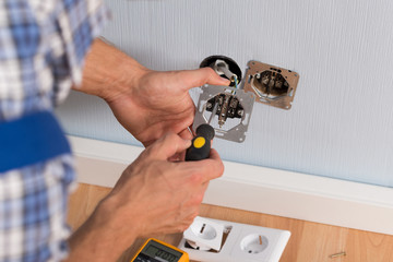 Electrician Hands Installing Wall Socket