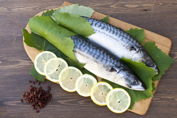 Fresh mackerel in grape leaves with lemon slices